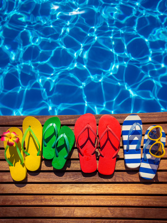 to flop: Multicolor flip-flops on wooden planks against blue water background. Summer family vacation concept