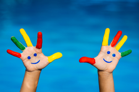 smiley: Smiley hands against blue water background. Summer vacation concept