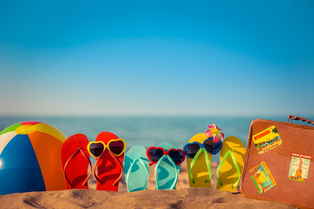 flip flops on the beach: Flip-flops, beach ball and suitcase on the sand. Summer vacation concept Stock Photo