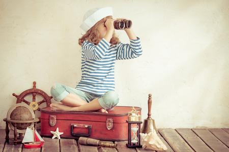 Gelukkig kind dat met vintage nautische dingen. Kid plezier thuis. Zomer zee droom en verbeelding. Avontuur en reizen concept. Retro getinte afbeelding