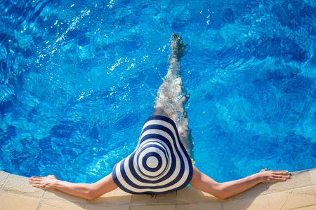 kapelusze: Młoda kobieta w basenie. Letnie wakacje koncepcji Zdjęcie Seryjne