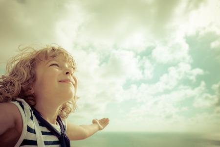 manos levantadas al cielo: Niño marinero mirando hacia el futuro contra el cielo de verano de fondo
