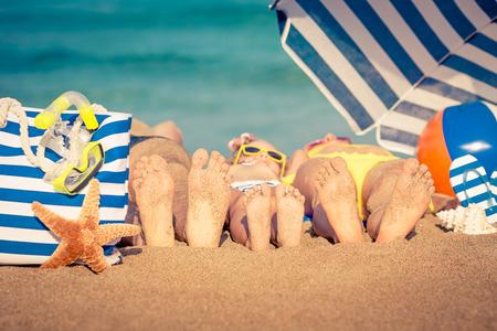 playas tropicales: Familia feliz que miente en la playa. Concepto de las vacaciones de verano