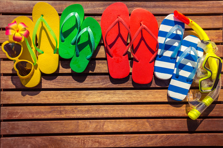 Multicolor flip-flops on wooden background. Summer family vacation concept Stock Photo