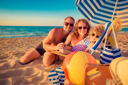 vacaciones en la playa: Familia feliz sentado en la cama solar. Hombre, mujer y ni�o que se divierte en la playa. Concepto de las vacaciones de verano