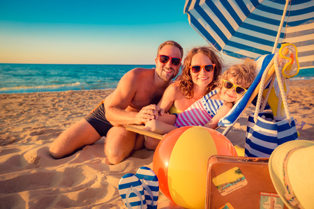 woman relaxing: Happy family sitting on the sunbed. Man, woman and child having fun at the beach. Summer vacation concept