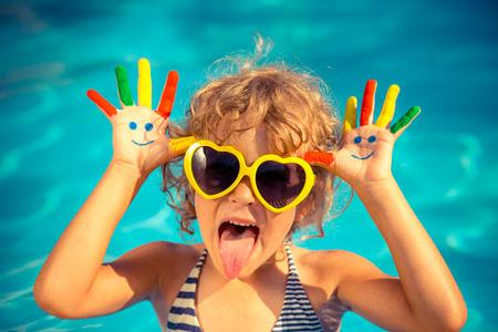 Niño divertido con el dibujo sonriente en las manos en la piscina. Concepto de las vacaciones de verano Foto de archivo