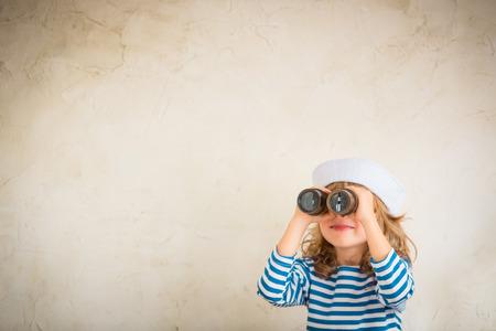빈티지 해상 쌍안경을 가지고 노는 아이 행복합니다. 아이는 집에서 재미. 여름 바다의 꿈과 상상력. 모험과 여행 개념입니다. 레트로 톤의 이미지