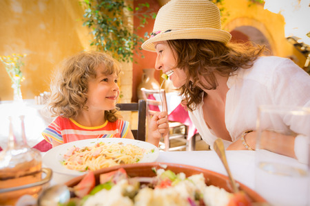 Madre y niño que se divierte en café del verano al aire libre