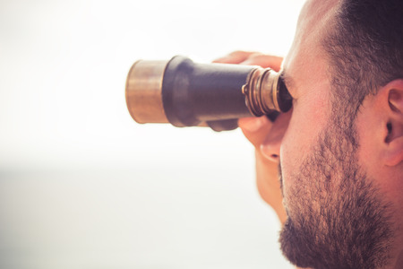 Sailor man looking through the binoculars against blue sky background