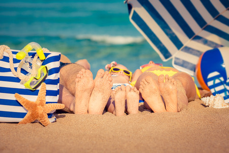 sunny beach: Happy family lying on the beach. Summer vacation concept