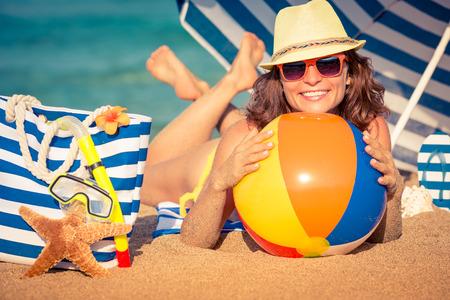 Mujer joven feliz acostado en la arena. Muchacha que sostiene la pelota de playa. Concepto de las vacaciones de verano