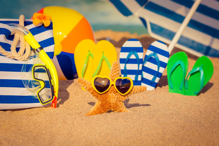 Flipflops beach bag and funny starfish on the sand. Summer vacation concept Stock Photo