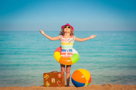 Happy child with vintage suitcase on the beach. Summer vacation and travel concept