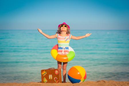 Niño feliz con la maleta de la vendimia en la playa. Las vacaciones de verano y el concepto de viaje