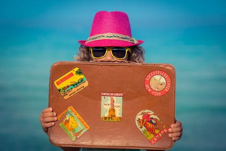 Gelukkig kind met uitstekende koffer op het strand. Zomer vakantie en reizen concept
