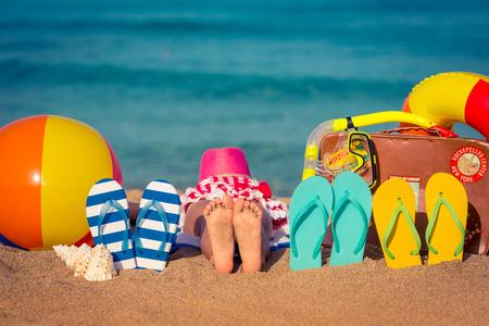 férias: Flipflops e os pés das crianças na praia. Conceito de férias de verão