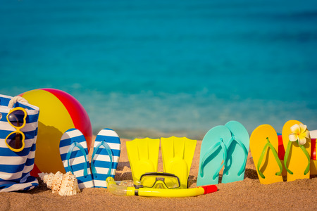 Flipflops beach ball and snorkel on the sand. Summer vacation concept