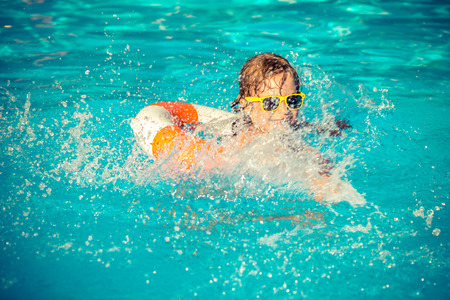 the pool: Happy child playing in swimming pool. Summer vacation concept Stock Photo