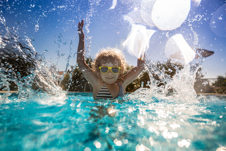 splash background: Happy child playing in swimming pool. Summer vacation concept Stock Photo