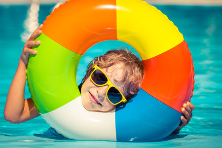 Happy child playing in swimming pool. Summer vacation concept Фото со стока
