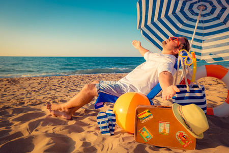 행복 한 젊은 남자가 해변에 앉아. 여름 휴가 개념