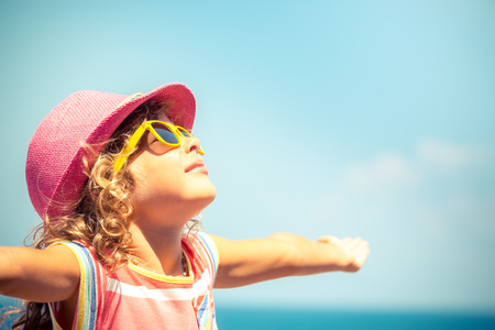 manos levantadas al cielo: Niño feliz contra el fondo de cielo azul. Concepto de las vacaciones de verano