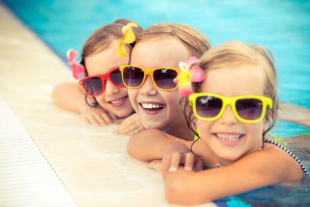lazer: Crianças felizes na piscina. Miúdos engraçados brincar ao ar livre. Conceito de férias de verão