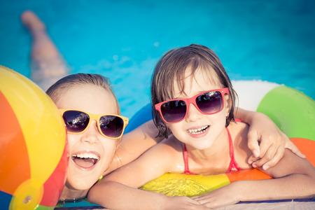 Счастливые дети в бассейне. Смешные дети, играя на открытом воздухе. Летние каникулы концепция