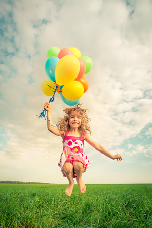 Having Fun: Happy child jumping with colorful toy balloons outdoors. Smiling kid having fun in green spring field against blue sky background. Freedom concept