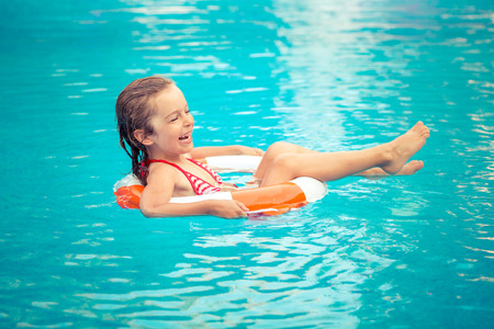 Happy child playing in swimming pool. Summer vacation concept Stock Photo