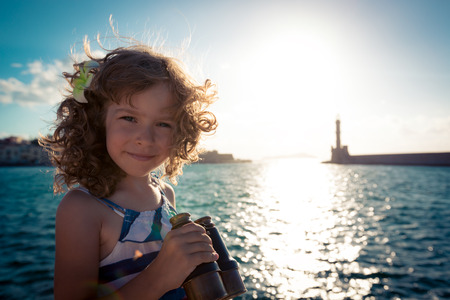 Sailor kid looking through the binoculars against blue sky background Stock fotó
