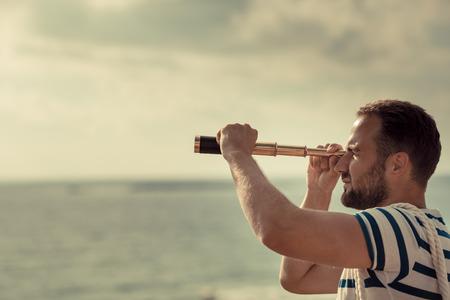 marinero: El hombre del marinero mirando a través de los binoculares contra el fondo de cielo azul