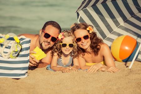 travel family: Familia feliz que miente en la playa. Concepto de vacaciones de verano. Imagen en tonos retro Foto de archivo