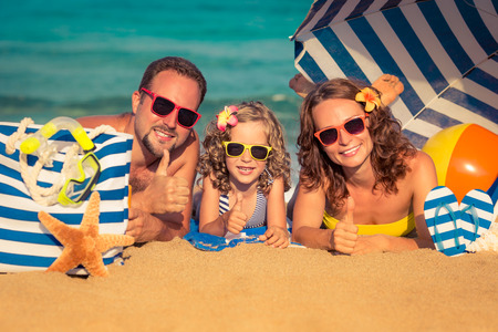 Happy family lying on the beach. People showing thumbs up. Summer vacation concept