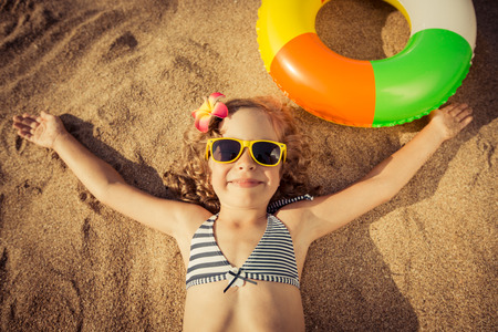 Happy child lying on the beach. Unusual top view portrait Stock Photo