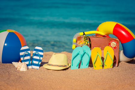 Flip-flops, beach ball and vintage suitcase on the sand. Summer vacation concept