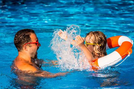 nadar: El ni�o feliz y padre jugando en la piscina. Concepto de las vacaciones de verano
