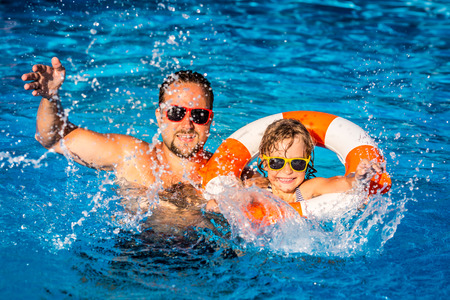 Happy child and father playing in swimming pool. Summer vacation concept