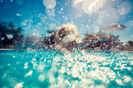 Happy child playing in swimming pool. Summer vacation concept Standard-Bild