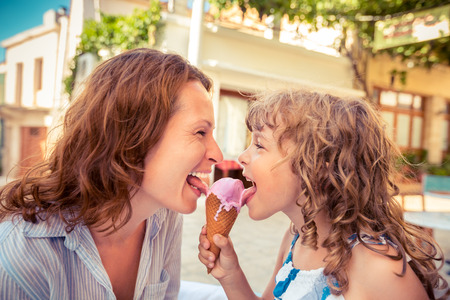 woman with ice cream: Mother and child eating ice-cream in summer cafe outdoors