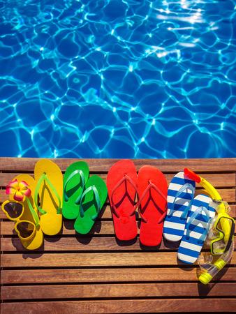 resor: Multicolor flip-flops på träplankor mot blå vattenbakgrund. Sommarfamilj semesterkoncept
