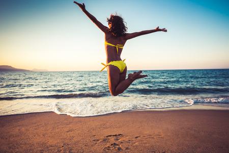 verano: Mujer joven feliz que salta en la playa. Las vacaciones de verano y concepto de la libertad