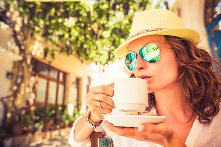 Young beautiful woman drinking coffee in summer cafe outdoors Stock Photo