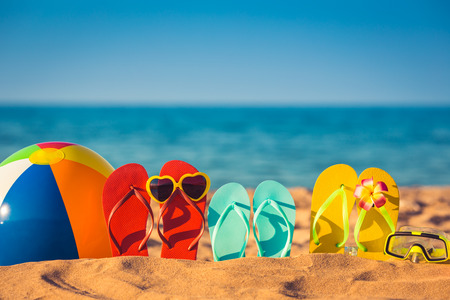 flip flops on the beach: Flip-flops, beach ball and snorkel on the sand. Summer vacation concept