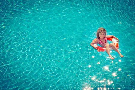 verano: Ni�o feliz que juega en la piscina. Concepto de vacaciones de verano. Vista superior retrato