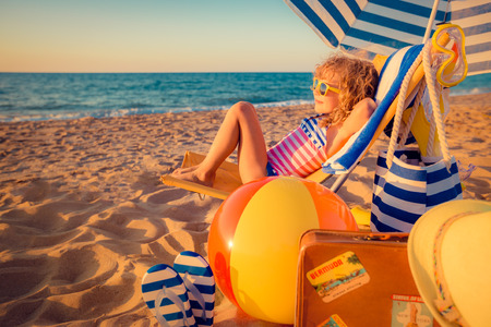 vacaciones en la playa: Ni�o feliz que se sienta en la cama solar. Cabrito divertido en la playa. Concepto de las vacaciones de verano Foto de archivo