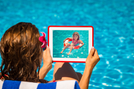 summer holiday: Woman holding tablet PC with black blank screen against blue water . Summer vacation concept Stock Photo