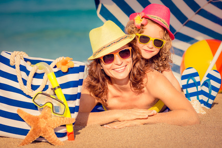 family fun: Happy child and mother lying on the beach. Summer vacation concept