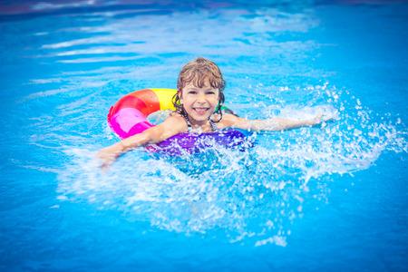 プールで遊んで幸せな子。夏の休暇の概念